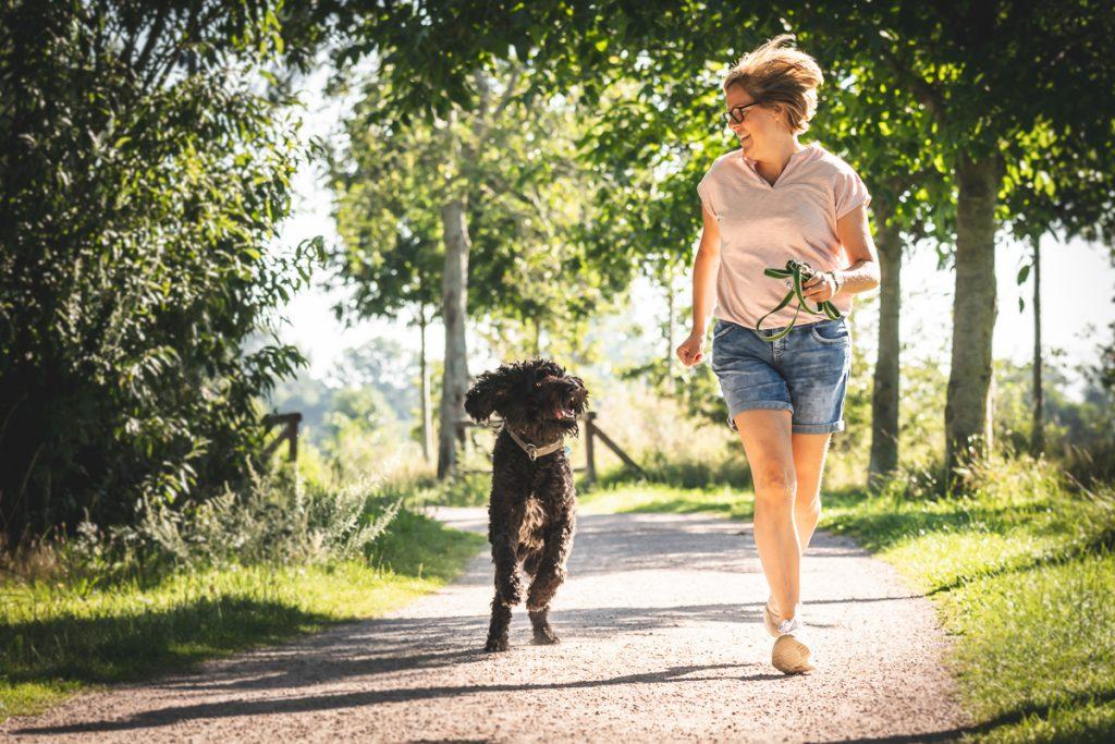 Schwarzer Labradoodle läuft neben seinem Frauchen. Foto: Kerstin Bittner